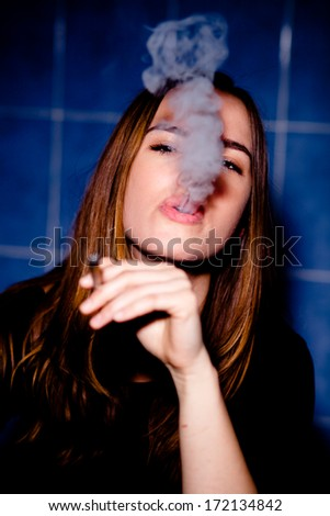 Young woman smoking a joint. Getting high in the bathroom. - stock photo