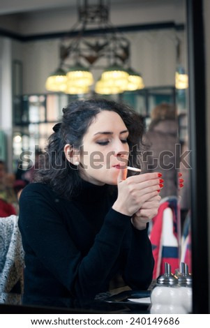 Young woman smoking in a stylish old European cafe - stock photo