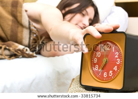 Young woman snoozing a red alarm clock - stock photo