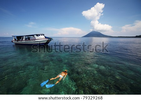 Young woman snorkeling in transparent shallow sea near boat - stock photo