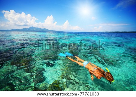 Young woman snorkeling over coral reef in transparent tropical sea. Bunaken island. Indonesia - stock photo