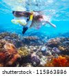 Young woman snorkeling over vivid coral reef in a tropical sea - stock photo