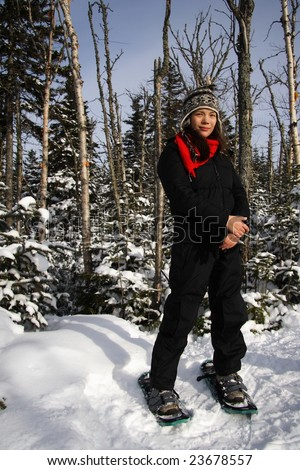 Young woman snowshoeing in pine forest near Baie Saint-Paul, Quebec, Canada