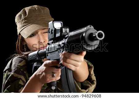Young woman soldiers with guns, isolated on black background