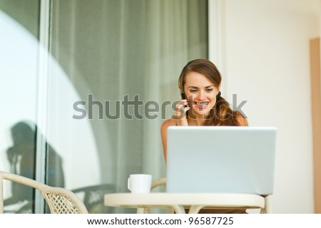 Young woman speaking mobile phone and looking in laptop