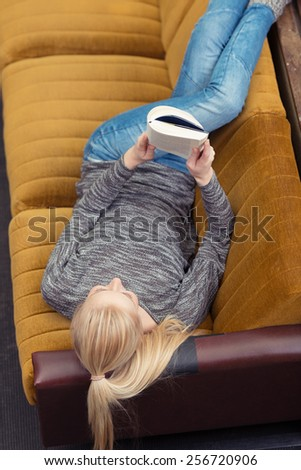 Young woman spending a relaxing day at home lying on a sofa reading a book with her legs raised on the back, view from above