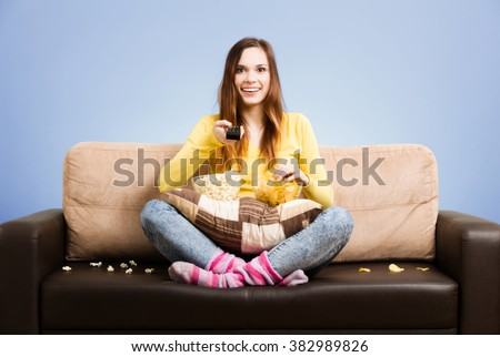 Young woman spends his free time watching TV on the couch at home, munching chips and popcorn. Gray background, easy to remove. - stock photo