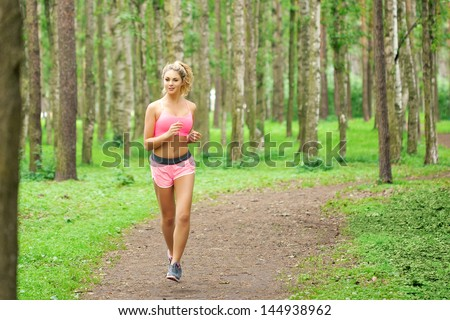 Young woman sports, running in the park - stock photo