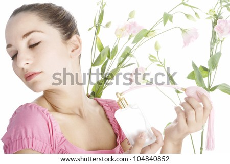 Young woman spraying herself with perfume, surrounded by blossom. - stock photo