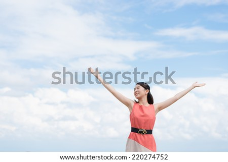 Young woman spreading arms on sky background.