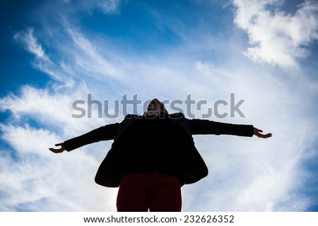 Young woman spreading arms towards the blue sky Silhouette - stock photo