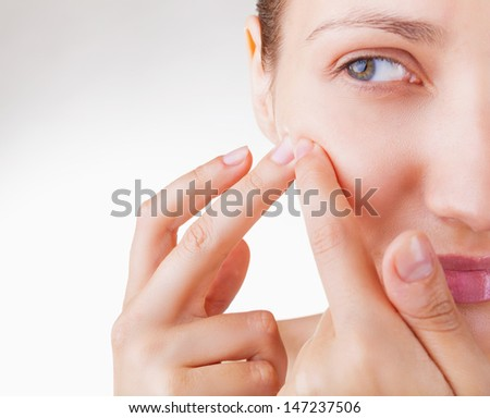 Young woman squeezing pimple on her cheek on white background - stock photo