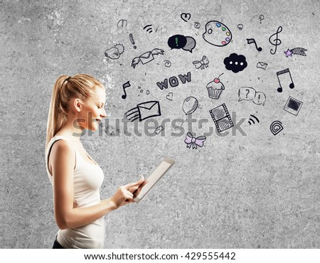 young woman standing against concrete wall and using  touch pad - stock photo