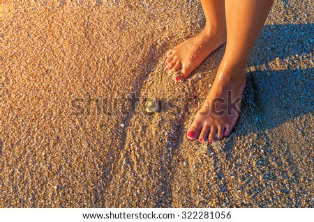 Young woman standing alone on the beach in the sunset - stock photo