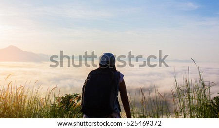 Young Woman standing alone outdoor with wild forest mountains on background Travel Lifestyle and survival concept rear view,Woman spreading hands with joy and inspiration in mountains.