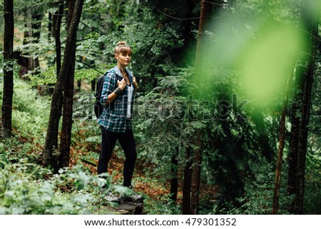 young woman standing among the trees of a forest with her backpack, watching and listening the nature