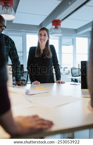 Young woman standing at table with colleagues during a meeting. Caucasian businesswoman smiling during a meeting with coworkers. - stock photo