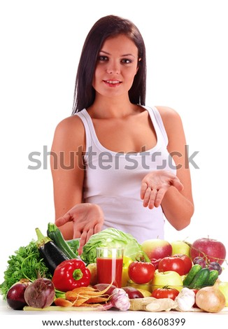 Young woman standing at the table with variety of fresh raw vegetables. Isolated on white.