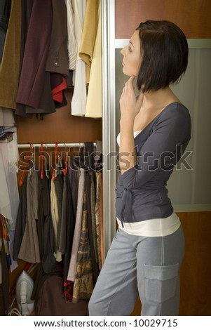 Young woman standing at wardrobe. She thinking what get dressed. - stock photo