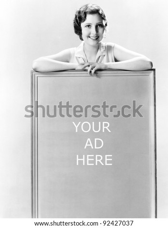 Young woman standing behind a sign - stock photo