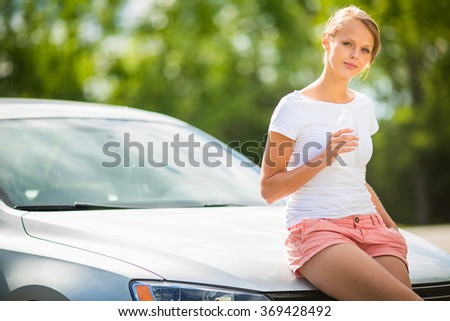 Young woman standing by her new car, having a refreshing drink of water before getting back on the highway during her long summer travel - stock photo