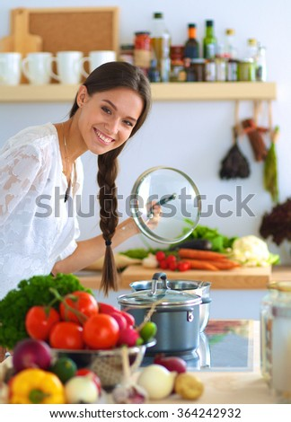 Young woman standing by the stove in the kitchen - stock photo