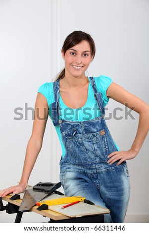 Young woman standing by workbench at home - stock photo