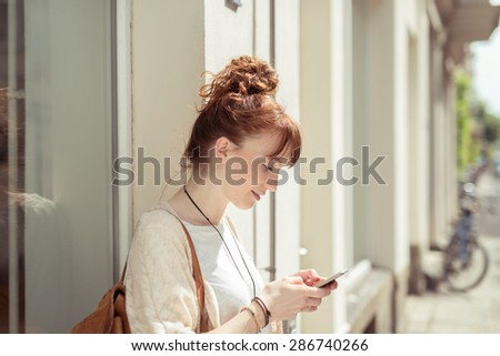 Young woman standing in an urban street reading a sms on her mobile phone with a serious expression, profile view - stock photo