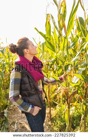 Young woman standing in cornfield - stock photo