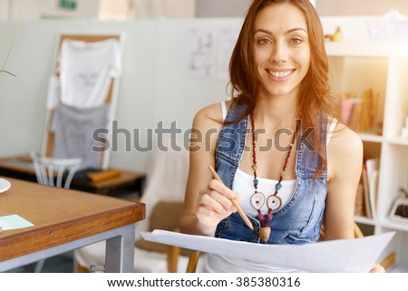 Young woman standing in creative office - stock photo