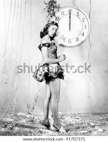 Young woman standing in front of a clock, celebrating New Years Eve - stock photo