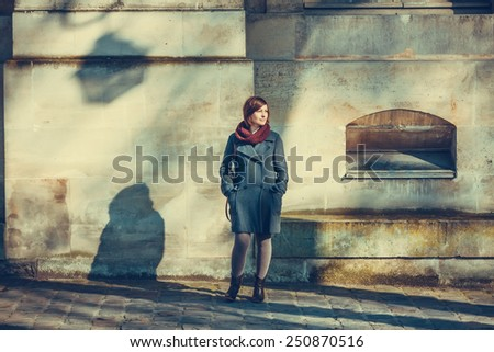 Young woman standing in front of a wall on a sunny day - stock photo