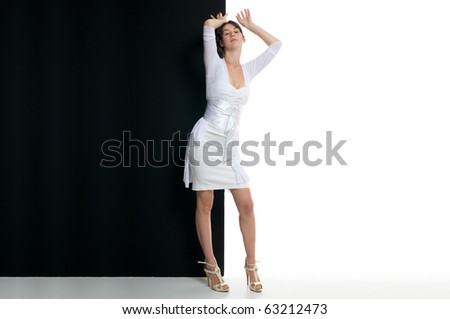 Young woman standing in front of black and white billboard - stock photo