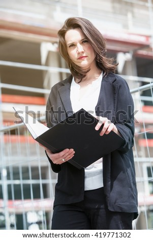 young woman standing in front of construction site and holding at book - stock photo