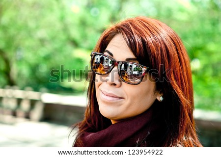 Young woman standing in front of green park trees with bright red hair headshot portrait. Photographed in the city with reflections in the lenses showing urban life. - stock photo
