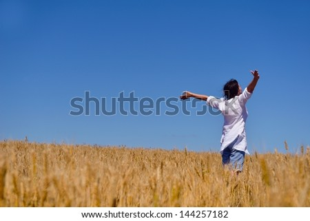 Young woman standing jumping and running  on a wheat field with blue sky the background at summer day representing healthy life and agriculture concept - stock photo