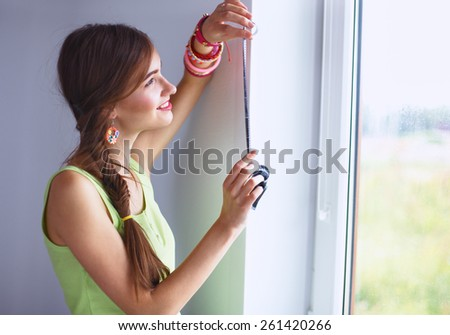 Young woman standing near dark wall, looking at window - stock photo