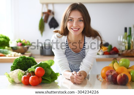 Young woman standing near desk in the kitchen . - stock photo