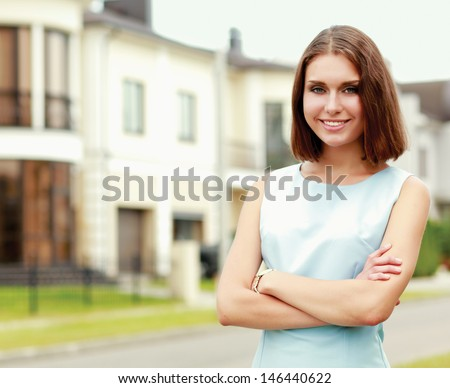 Young woman standing near house, isolated on white background - stock photo