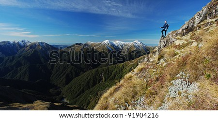 Young woman standing near mountain top overlooking peaks beyond - stock photo