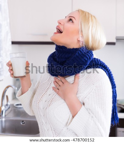 Young woman standing near sink with gargle solution