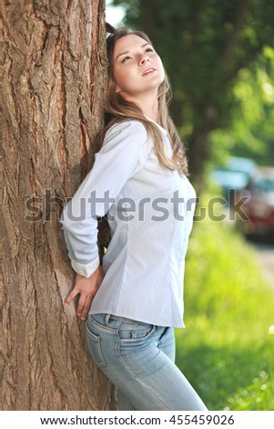 young woman standing near tree and enjoying beautiful  nature