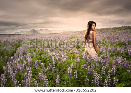 young woman standing on a meadow at sunset