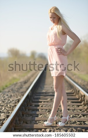 Young woman standing on a railroad - stock photo