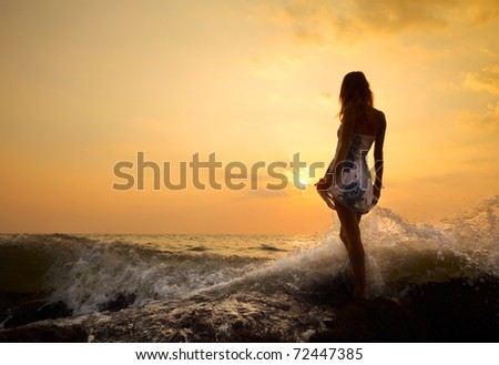 Young woman standing on a rock in sea and holding her dress. - stock photo