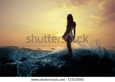 Young woman standing on a rock in sea and holding her dress. Toned - stock photo