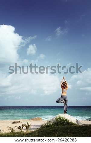 Young woman standing on a rock on a beach and stretching - stock photo