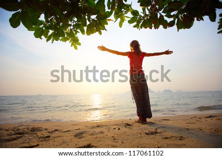 Young woman standing on a tropical beach with rised hands and looking to a sun - stock photo