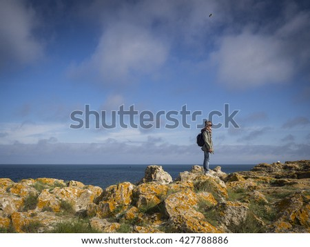 Young woman standing on cliff with a smile on her face and enjoying sea view.