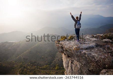 Young woman standing on cliff with outstretched arms and enjoying valley view - stock photo